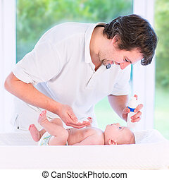 Young loving father changing diaper of his newborn baby son,...