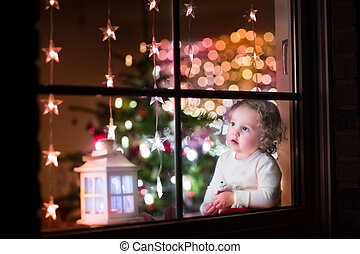 Girl at Christmas eve - Cute curly toddler girl sitting with...