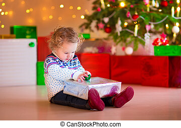 Little girl opening her Christmas present