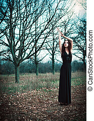 Cute goth girl wearing black dress stands amongst autumnal...