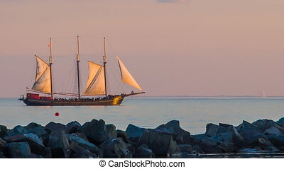 Sailboat in sunset - Sailboat moving on a sea in sunset