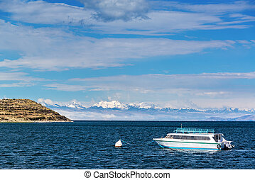 Boat and Andes Mountains - View of a boat on Lake Titicaca...