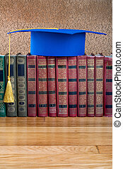 Graduation mortarboard on top of stack of books on abstract...