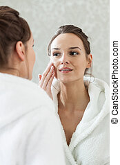 Woman looks at herself in the mirror in spa