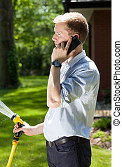 Businessman watering grass in a garden, vertical