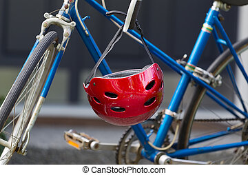 Bright red bicycle helmet hanging from handle bars