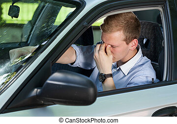 Tired businessman driving a car - View of tired businessman...
