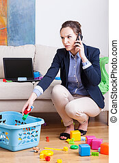 Woman working and organising toys - Young mother talking on...