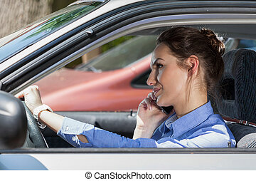 Woman on phone in car - Young woman talking on the phone...