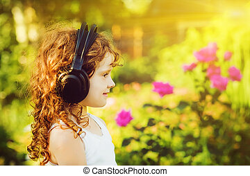 Little girl listening to music on headphones in a summer...