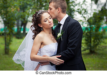 beautiful wedding couple - young handsome groom kiss his...