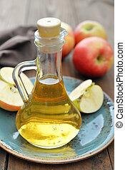 Apple cider vinegar in glass bottle and fresh apples on...