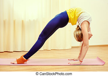backbend pose - Slender athletic girl doing yoga exercises...