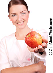 Nurse offering an appleto the camera - A smiling...