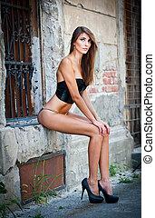 Sexy girl in bikini posing fashion near red brick wall on...