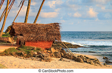 Summer hut on ocean shore - Summer hut with straw roof on...