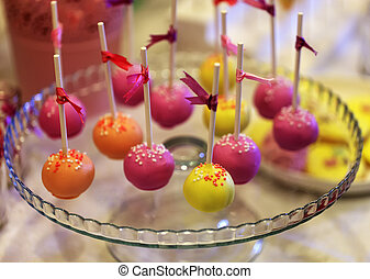 Colorful cake-pops on a glass plate with satin ribbons on...