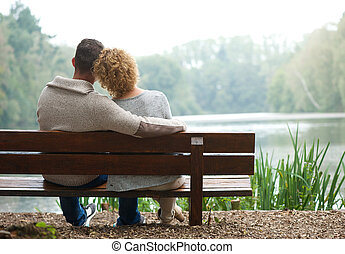Rear view couple sitting on bench outdoors - Rear view of a...