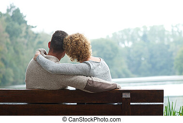 Couple sitting on bench by the lake