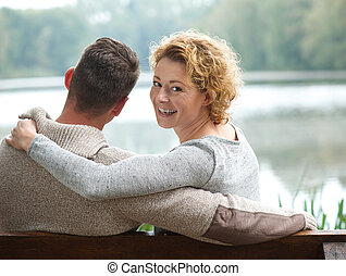 Happy couple sitting on bench outdoors - Portrait of a happy...