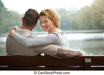 Couple sitting on bench by a lake - Portrait of a couple...