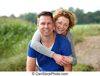 Smiling woman hugging her boyfriend outdoors - Close up...