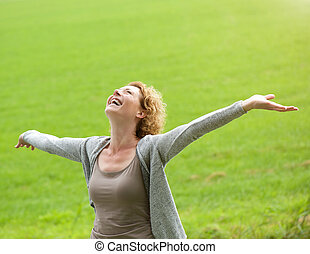 Cheerful older woman smiling with arms outstretched -...