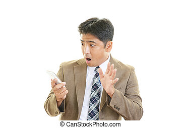 Surprised Asian businessman - Business woman holding a smart...