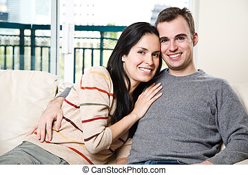 Happy couple relaxing at home - A happy couple sitting on...
