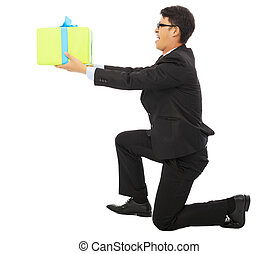 young Business man holding a gift box and kneel. isolated on...