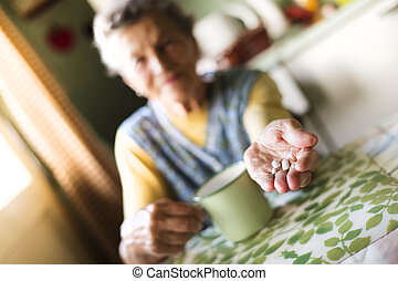 Old woman taking pills - Old woman is taking pills in her...
