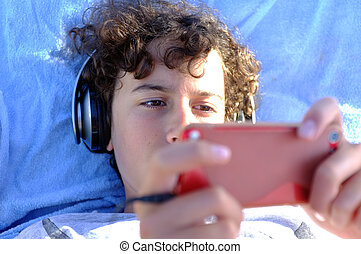 Young boy playing with his gadget - Young teen boy is...