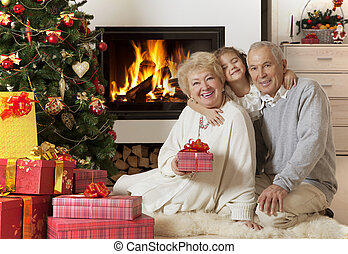 Senior couple with granddaughter enjoying Christmas - Happy...