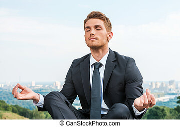 Businessman meditating Relaxed young man in formalwear...