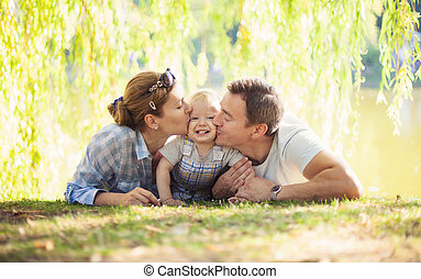 Happy parents kissing toddler boy. Father, mother and son...