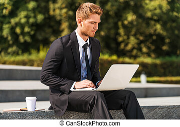 Working outdoors. Confident young man in shirt and tie...