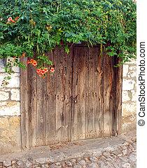 Old wooden door with flowers on top