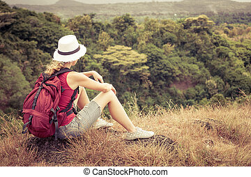 tourist with backpack relaxing on rock and enjoying admiring...