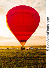 Hot air balloons landing in a field during sunse