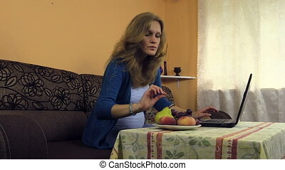 girl laptop vase fruit - young pregnant woman work at home...