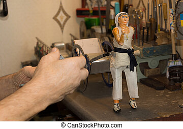 Man working on a model of a woman and cart - Close up of the...