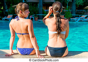 wo girls sitting on the edge of the pool in a swimsuit