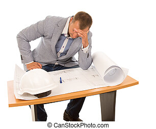 Architect or builder studying a blueprint sitting at a small...