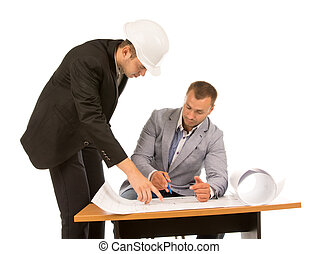 Two building contractors discussing a blueprint of a project...