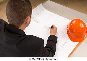 Young architect modifying a building plan - Over the...