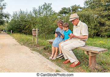 Grandchild and grandmother using a tablet outdoors -...
