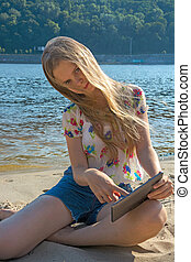 Girl on the beach with the tablet - Girl in bright clothes...