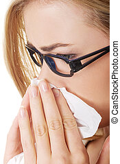 Sick woman blowing her nose