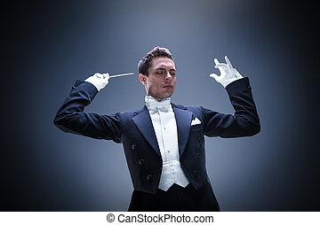 Performer - Young man in tuxedo conducting