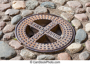 Old steel sewer manhole on the cobblestone road. Text on...